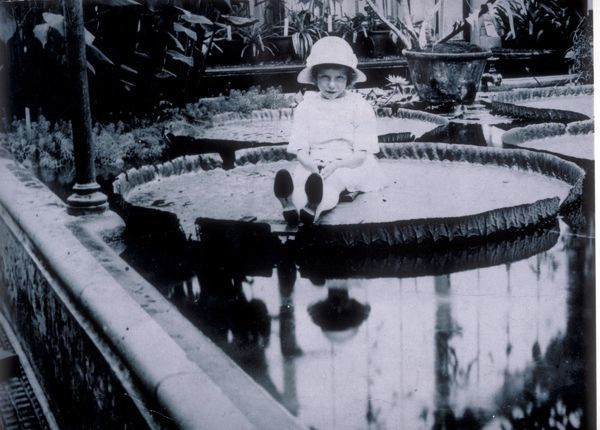 """Miss Cotton"" posing on the leaf of giant waterlily Kew Gardens, 1923. © RBG KEW"