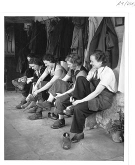 Women gardeners put on their clogs ready for work, World War II